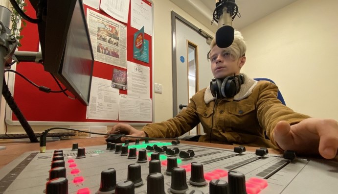 Young man sat at a radio mixing desk.
